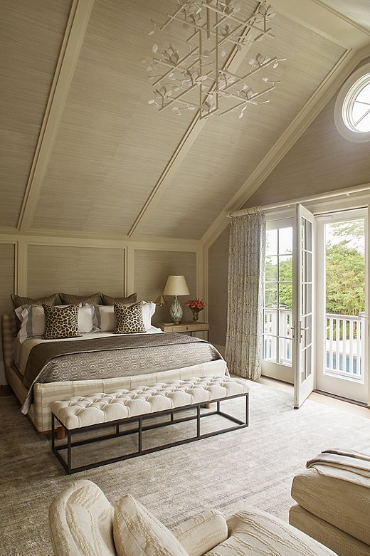 Maraand Jessie extended the grass-cloth wallpaper from the walls up the vaulted ceiling. The room feels much cozier as a result. An oversized chandelier also makes the scale of the room feel much more intimate.