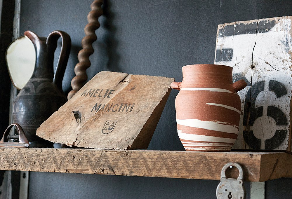 Greek amphora pottery is a repeated motif in Mancini's designs: She displays a few of her favorites on a rustic shelf above her workbench.