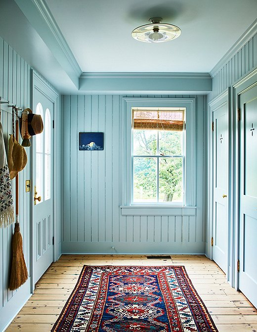 Farrow & Ball's Skylight sets the tone for this pass-through area. Teamed with an intricate runner and light wooden floors, the wall color feels bright and happy.