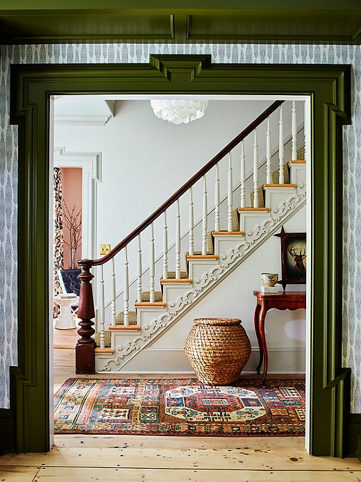 Farrow & Ball's Bancha paint color on the molding creates a striking green contrast to the rest of the living room. The entryway features delicate woodwork along the staircase. The vintage runner is part of Hendrick Churchill's collection of heirloom rugs.