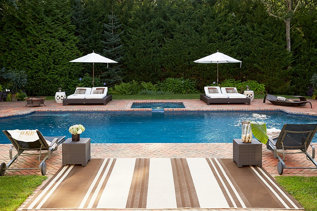 This poolside boasts plenty of lounge chairs and other seating—plus an outdoor rug that helps dry off wet feet before they step into the house.
