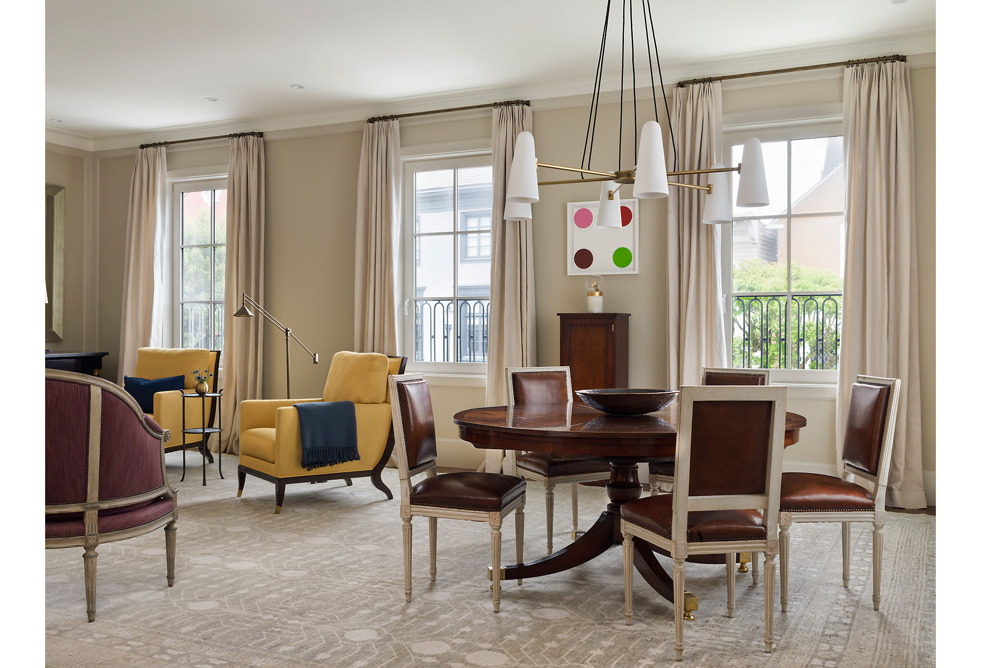 Heather included a more traditional aesthetic for the living room to counterbalance the modern art in the home. She juxtaposed pieces by Andy Warhol and Damien Hirst with Louis XVI chairs and dark wood furniture. (For similar chairs, see the Exeter Side Chair in Saddle Leather.)