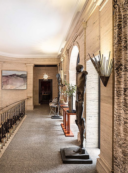 On the second-floor landing, designer Cynthia Spence used eye-catching sconces and life-size sculptures to create a moment of grandeur. Photo courtesy of Cynthia Spence.