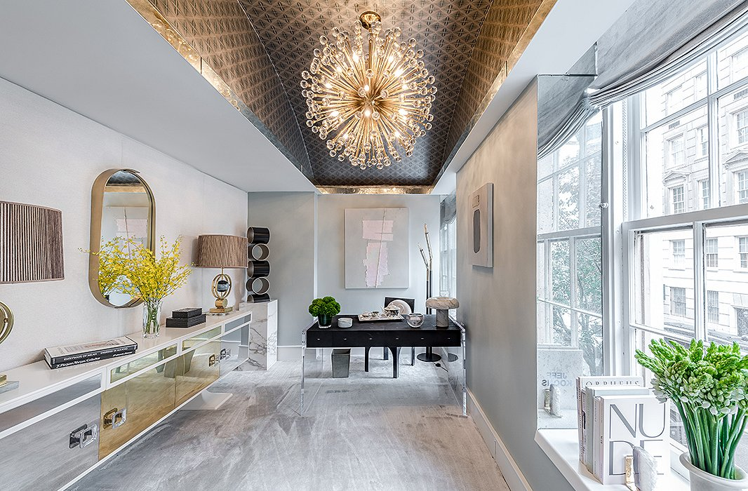 "Designer Natalie Kraiem created her rendition of a ""winter wonderland"" with marble, metallic wallpaper, and all things mod. A pendant light bursting with glass and brass crowns the space. Photo by Alan Barry."