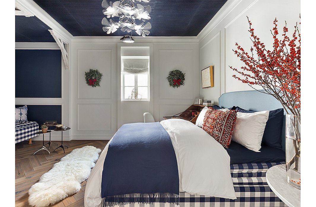 A bedroom by Sara Touijers evokes a Nordic winter with blue-and-white gingham, barn-style trusses, and a sheepskin throw. Wreaths and bittersweet branches play up the holiday theme. Photo by Regan Wood Photography.