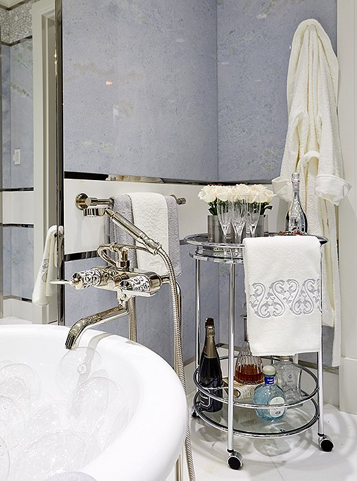 Holiday House founder Iris Dankner's elevated take on a master bath brings the idea of an at-home spa day to new heights. Equipped with a freestanding soaking tub, a fully stocked bar cart, and walls of pale-blue onyx, the room was designed to soothe the senses.