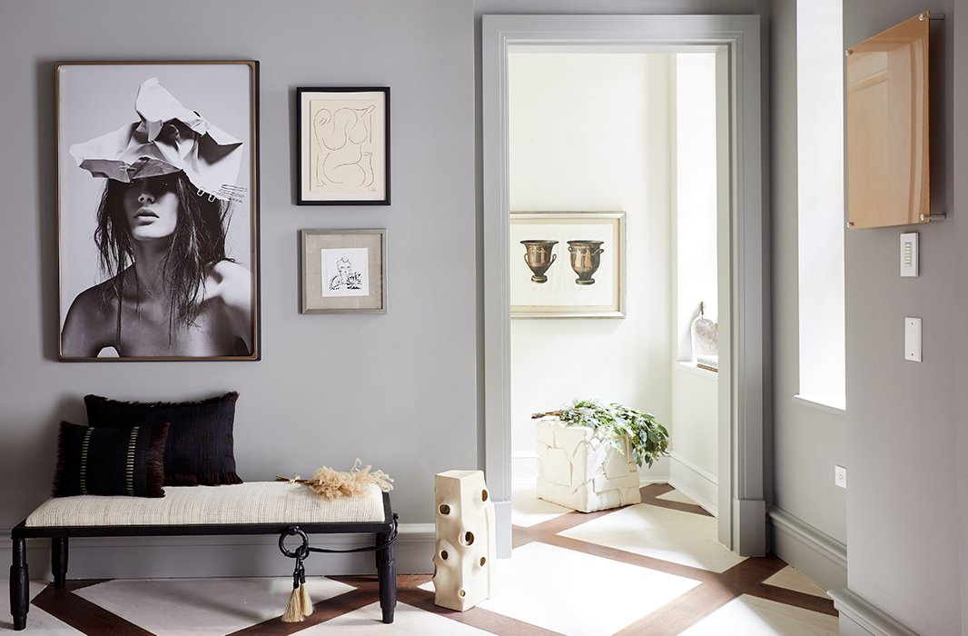 "For the home's foyer, Gabriela Gargano of Grisoro Designs opted for a gallerylike space of art and fine furniture. Along one wall, an iron bench with a seat covered in woven horsehair rests beneath a fashionable black-and-white photograph. ""I drew inspiration from the weathered hues of excavated artifacts and selected a deep yet muted palette,"" notes Gabriela in the Holiday House catalog."