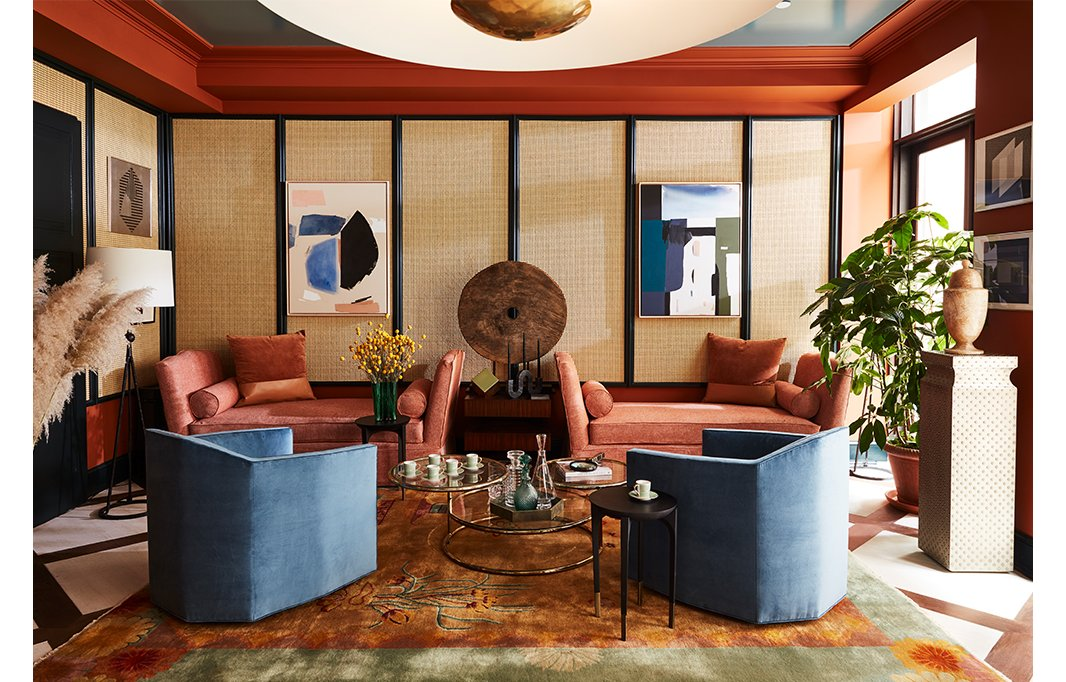 An antique Thai cart wheel from FEA Home makes for an artful focal point between two dusty-pink daybeds. The triple-tiered vintage brass coffee table mimics the lines of the room's saucerlike pendants, and a Chinese Art Deco-style rug from Rahmanan Rugs adds color and movement.