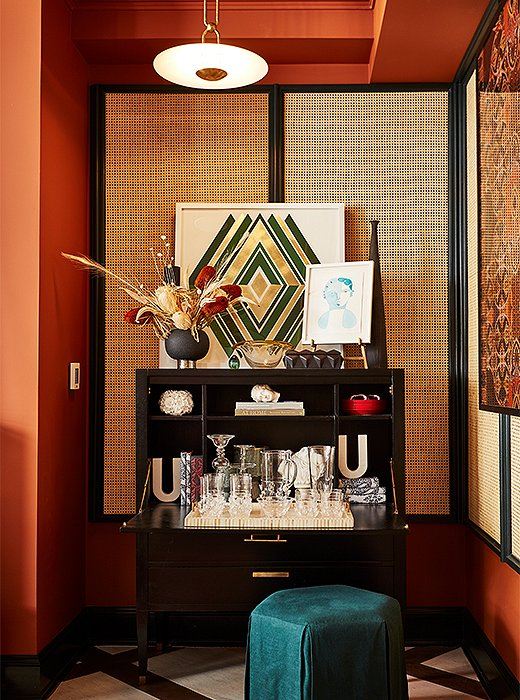 Crowned with a bold geometric print from artist Dawn Wolfe, a black Ave Home secretary doubles as a chic bar. The linen ottoman repeats a cool turquoise hue used used sparingly throughout the space.