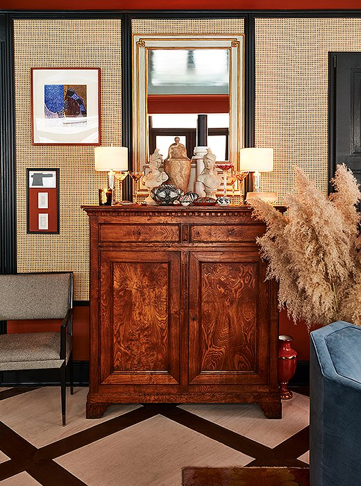 A Federal-style walnut chest speaks to classic American design. On top, antique treasures from Thailand, China, and Japan lend a global layer between two small nickel table lamps.