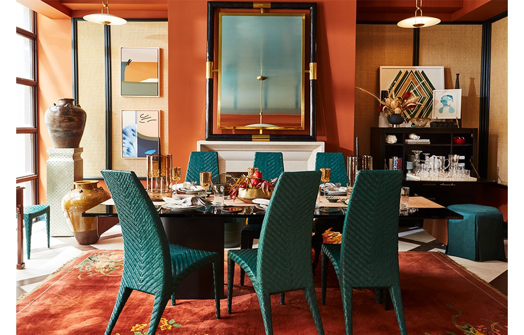Vintage turquoise chairs from Iconic Design Gallery surround a dining table by Kara Mann for Milling Road. The Chinese Art Deco-style rug is from Rahmanan Rugs and brings the warmth of the walls to the floor. The pendant lights are by Ralph Lauren Home.