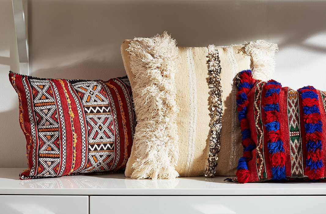 Moroccan Berber textiles encompass a number of styles. On the left, a hand-stitched geometric pillow; in the center, a wedding-blanket style; on the right, a pillow featuring intricate embroidery and fringe.