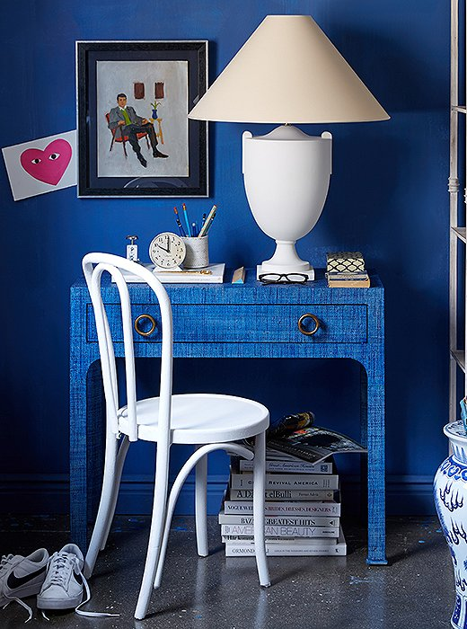 A deep-blue wall highlights the graceful silhouettes of the white lamp and the Thonet-style chair.