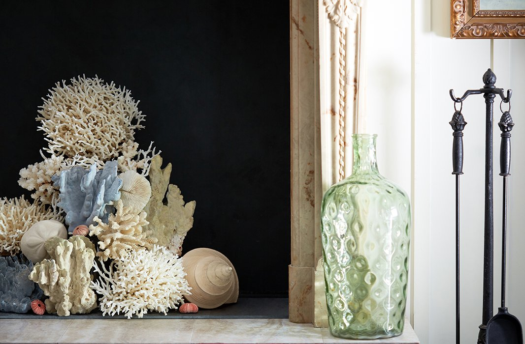 Let your fireplace have its moment in the sun with a beautifully beachy display of coral. Stick to one or two colors for a pulled-together look. Photo by Tony Vu