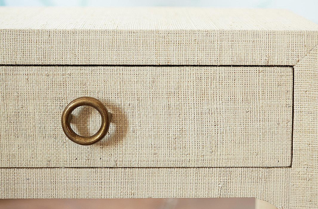A brass-tone drawer pull adds modern contrast to an intricate raffia finish.