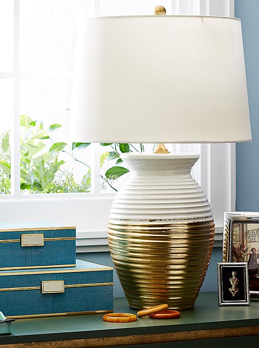 Featuring a body brushed with gold leaf and a hardback silk drum shade, the Ada Jar Lamp is a glamorous, statement-making addition to any room.