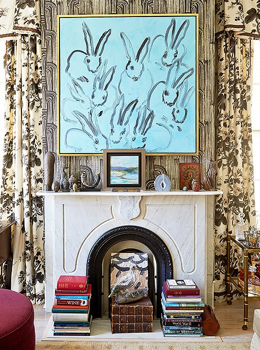 Stacks of books, sculptural objets, and leaning artwork—both on the floor and on the mantel above—give this fireplace an artfully collected look. Photo by Tony Vu