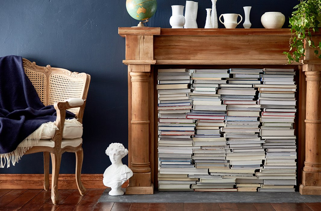 An ideal marriage of style and function, this fireplace display frees up major bookshelf space while creating a cozy, eclectic vibe. Turn the spines to the side for a more uniform look. Photo by Tony Vu