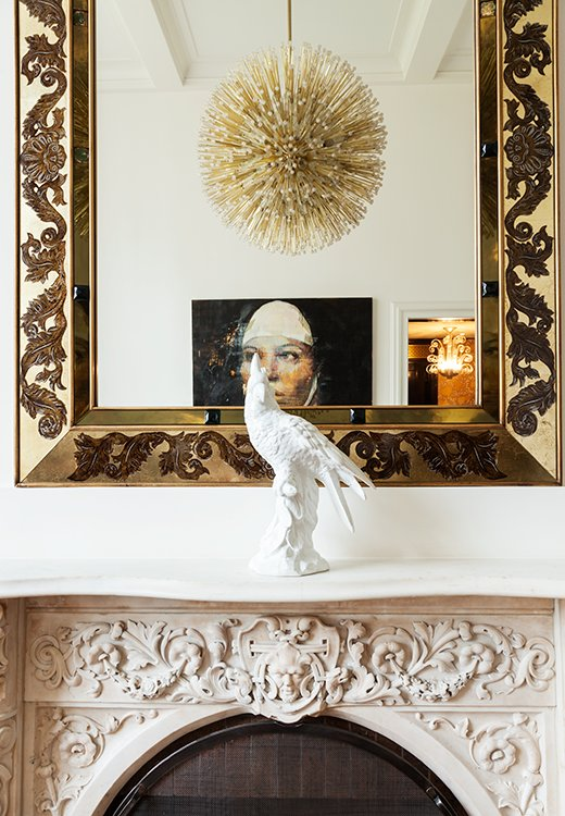 An intricately carved marble mantel is one of Smith's favorite room features. Above it hangs an églomisé mirror from the 1940s.