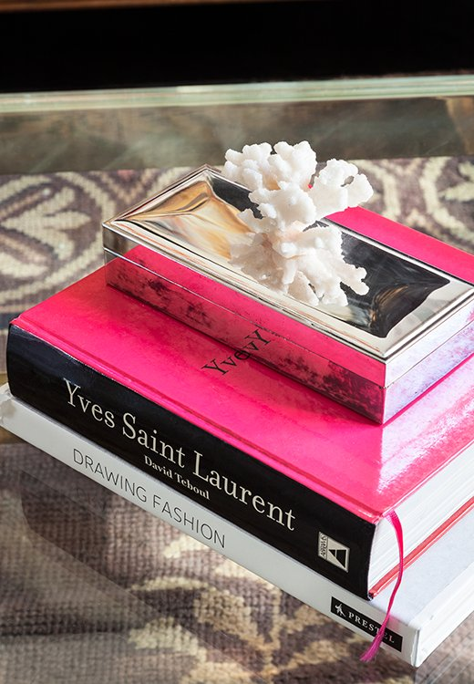 On the coffee table: a stack of fashion books (what else?). A metallic coral-topped box adds shape and shine.