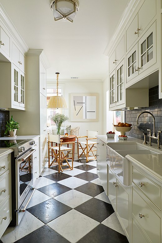 The kitchen received the most attention in Jeremy's design. He gutted the entire spacebefore introducing new appliances, flooring, and tiles. Abstract art at the end of the galley adds a fun touch to the more traditional black-and-white flooring and color palette.