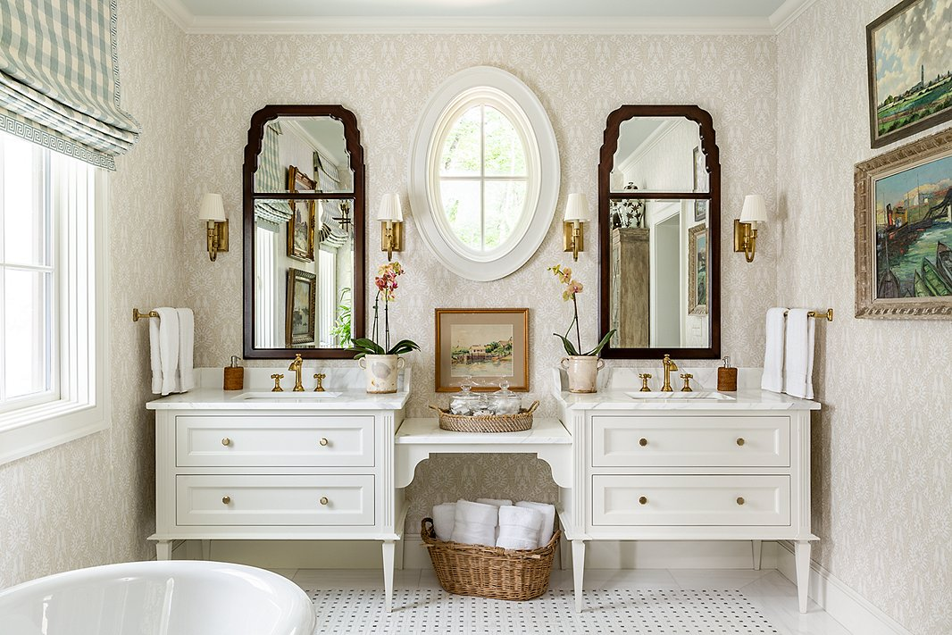 James went light and airy in the main bathroom. Rattan accents, wooden wall mirrors, and artadd warmth.