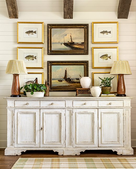 The casual elegance of the framed fish paintings point to the home's proximity near the water in a classic way.