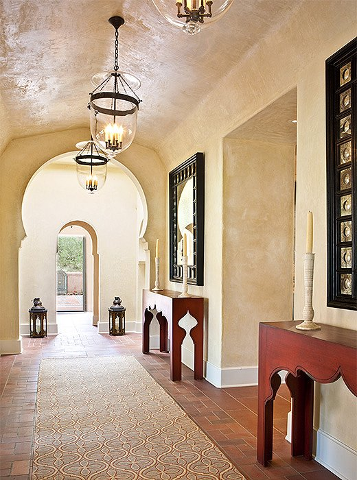 A horseshoe arch and custom consoles featuring a tented motif speak to the home's Moroccan-inspired design.