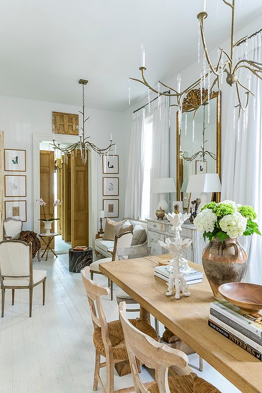 In a living/dining space, Julie paired twin chandeliers—the Audubon style from her collection—that drip with icy crystals.