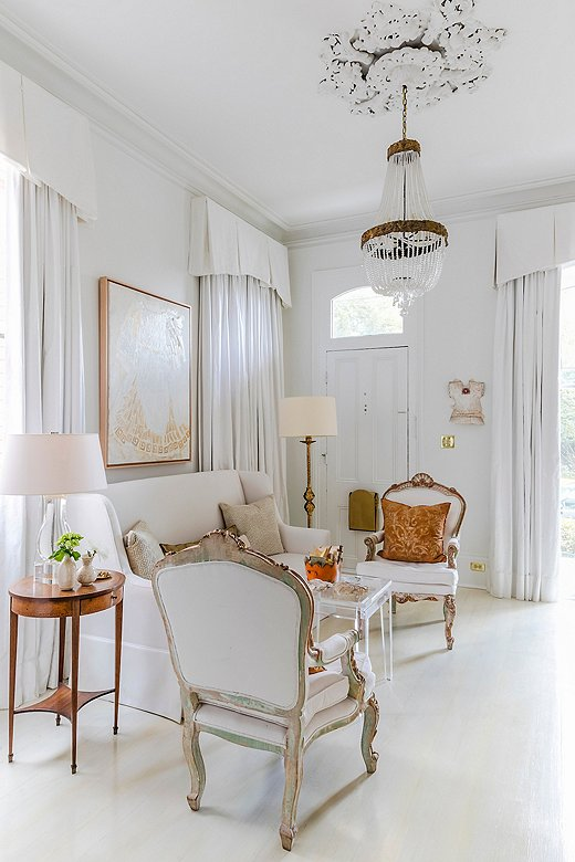 An embellished ceiling medallion paired with a beaded crystal chandelier makes a striking statement in a sitting room. Find a similar chandelier here.