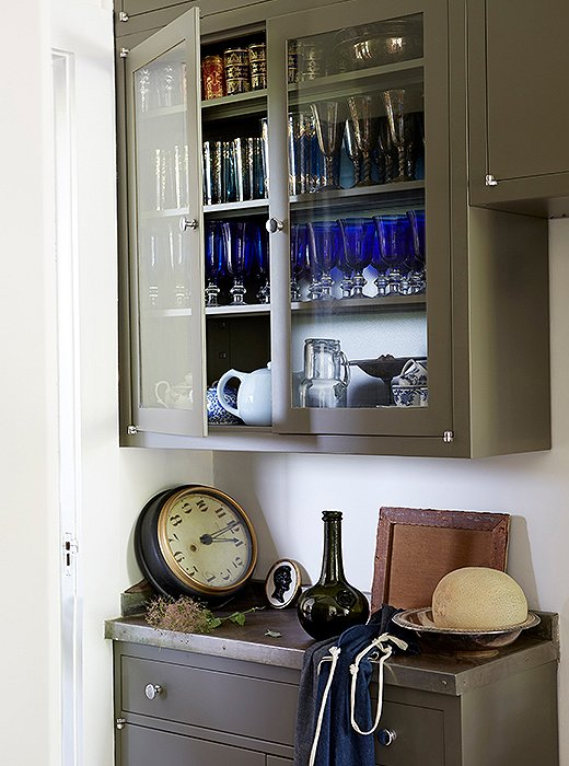 Cabinets in the butler's pantry house the couple's collection of vintage glassware and a trio of teapots.