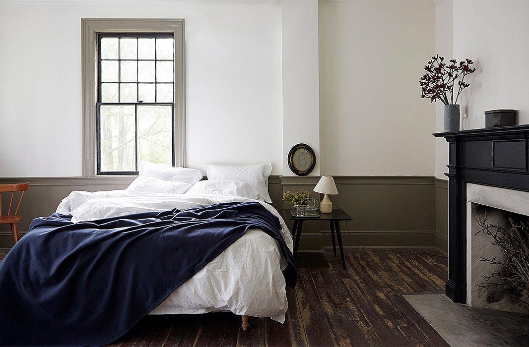 A navy Faribault blanket complements crisp white pillowcases and a heavenly duvet cover by Matteo in one of the guest suites. Frank sourced the bedding (and the vintage Paul McCobb side table) on One Kings Lane.