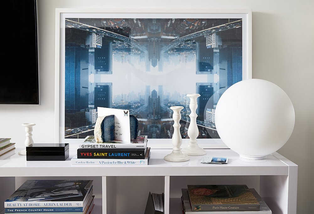 Alongside the flat-screen television, a leaning photograph by Daniel Håkansson stands as a visual counterpoint and striking display amid white accents.