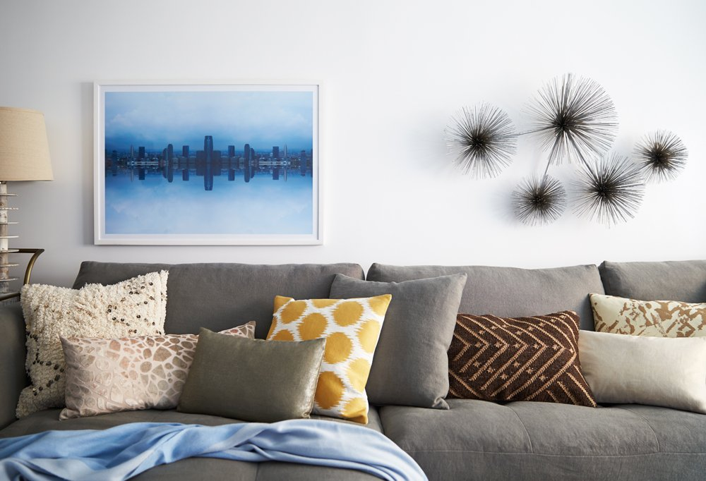 A photographic print by Daniel Håkansson hangs alongside a metal wall sculpture by by C. Jeré above colorful and richly textured pillows on the sectional.
