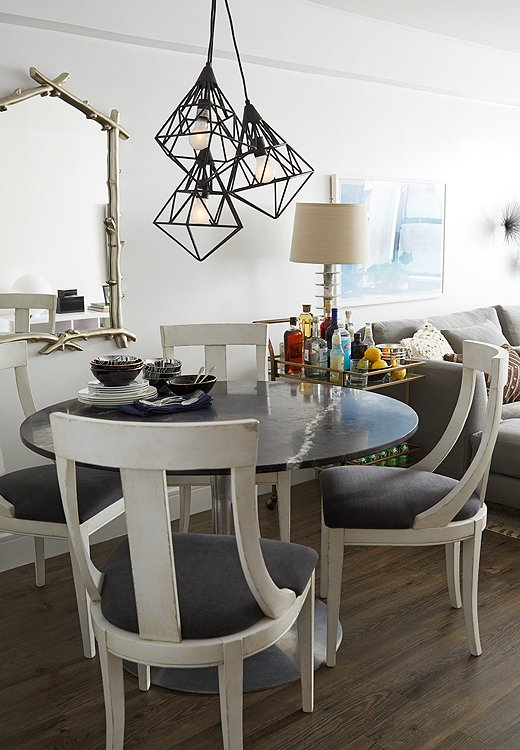 "A vintage marble-top table centers the dining area. ""Since it's a small dining space, I went with a circular table so that there's room to move around it,"" Andrew explains."