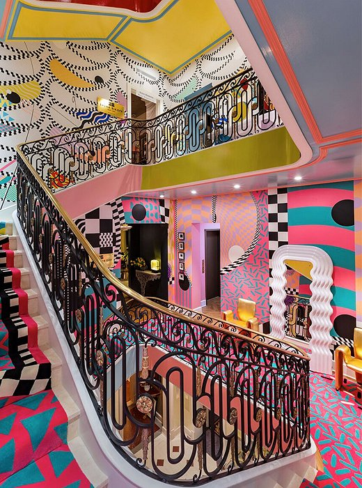 A surreal stairway aptly reflects designer Sasha Bikoff's creative genius. Nods to the Memphis Group abound with walls covered in zigzags, squiggles, and triangles, while a seemingly endless carpet transports the mind to Alice's Wonderland.