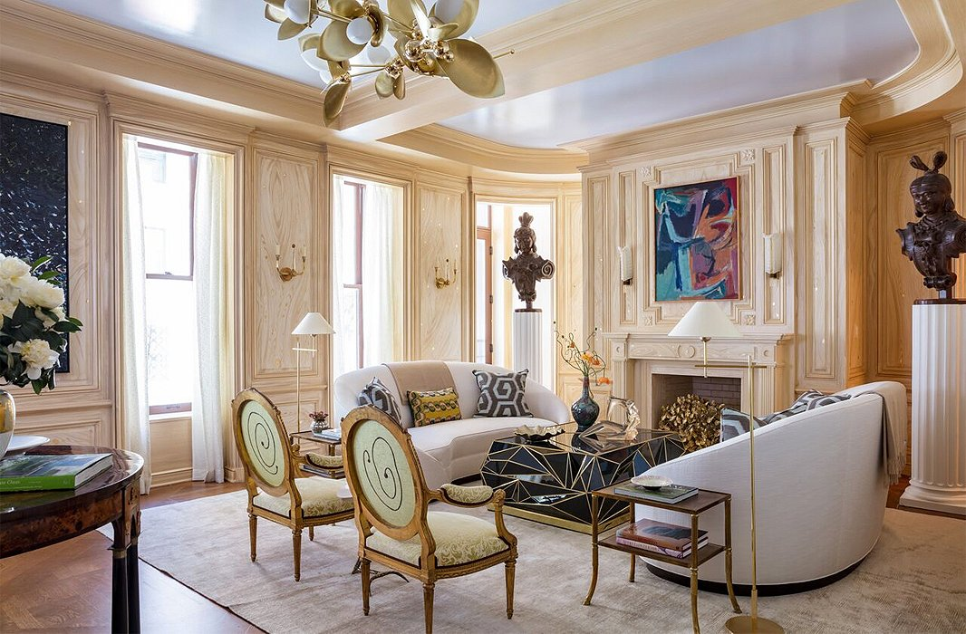 "Parisian romance meets New York sophistication in this living room by show-house chair Bunny Williams. Oak paneling flecked with gold picks up on the shimmer of a silk rug and Louis XV chairs dressed in Fortuny. As to inspiration, it wasn't a pied-à-terre or a Park Avenue penthouse that came to Bunny's mind, but a treehouse—""one where you can look at the sky through gilded leaves and watch a spider make a giant cobweb,"" she says."