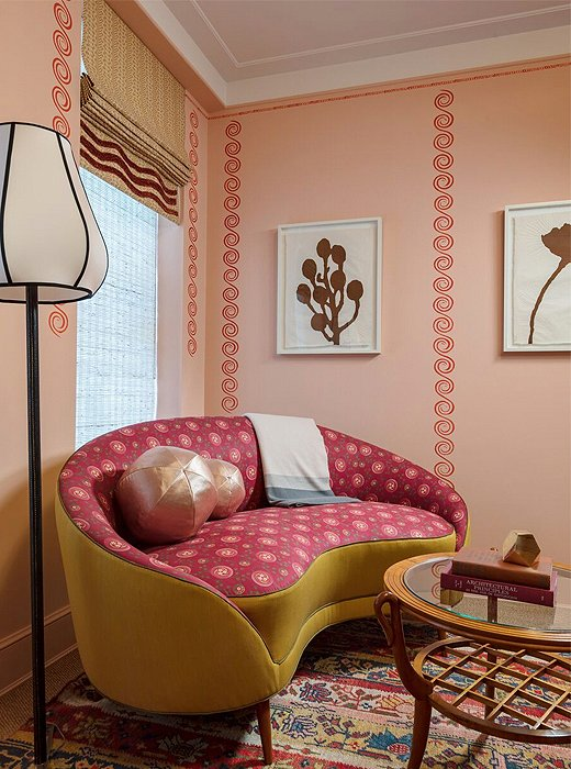 A vignette in a guest room by Katie Ridder speaks to the designer's take on a place of solace within the confines of a city. Here, a curvilinear settee with a wavelike effect is anchored by an Oushak rug locked in elegant conversation with the room's many pinks and reds.