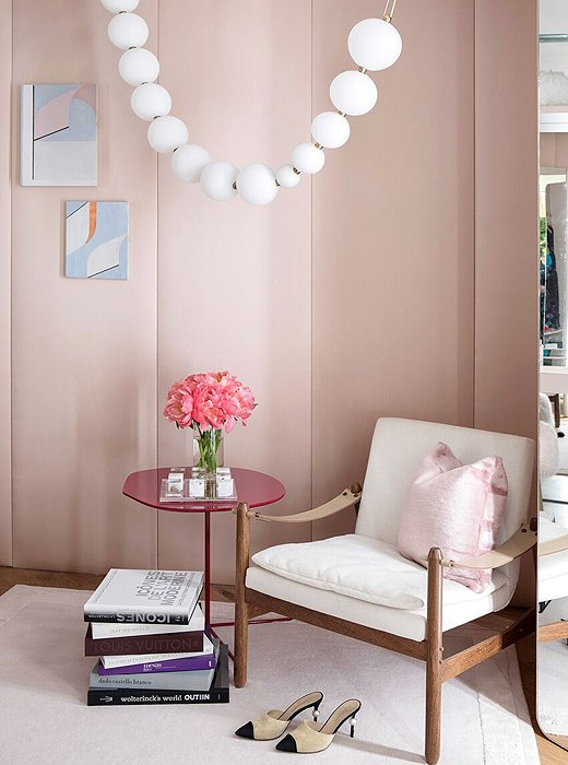 A sculptural light from Semeur d'Étoiles reads like a string of pearls in this dressing room by Marcia Tucker. Casually stacked books on style and a pair of Chanel pumps give guests a clear idea of the woman in Tucker's design vision.