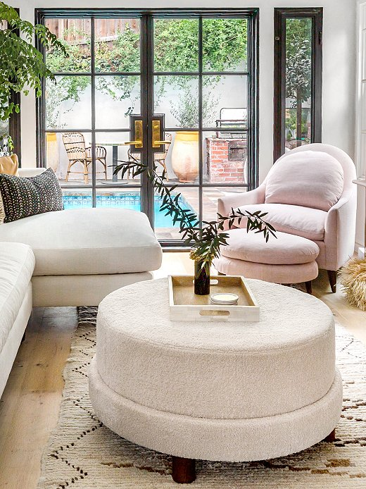 The Cutler Shearling Ottoman serves as a coffee table; just behind are the Lowell Linen Chair and the Lowell Linen Footstool.