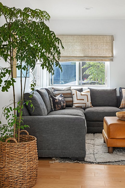 The Morris Crypton Sectionalis styled with Kim's global-inspiredpillows (from left: Nora Lumbar Pillow, Wren Pillow, Olivia Pillow, and Avery Pillow). Also shownis the Cutler Leather Ottoman.