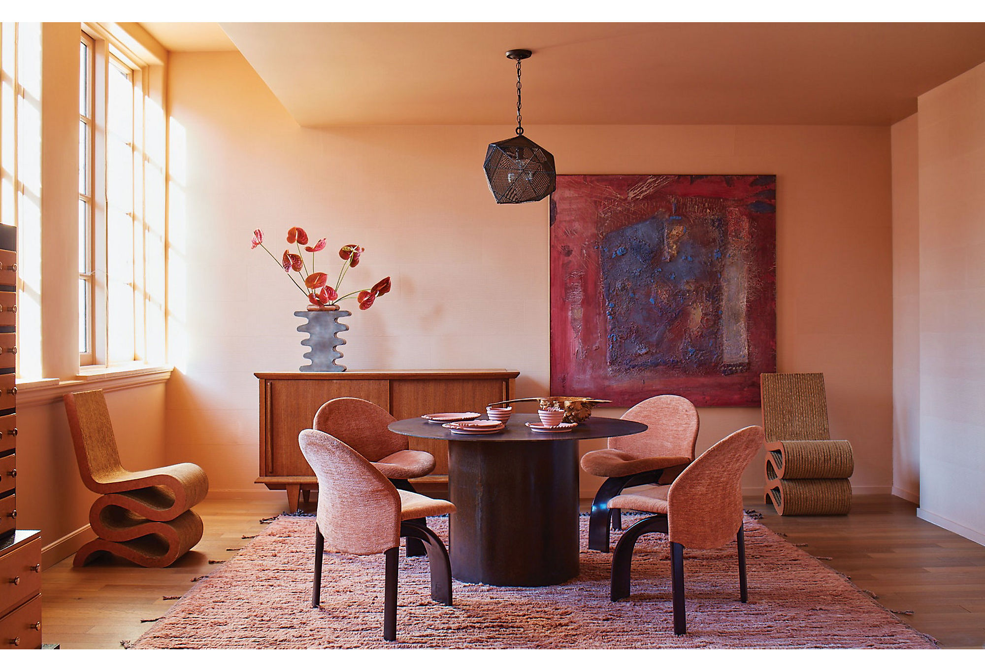 Faded Terracotta on the walls breathes life into this dining room, tying together the complementary textures and dynamic forms. Photo by Trevor Tondro.