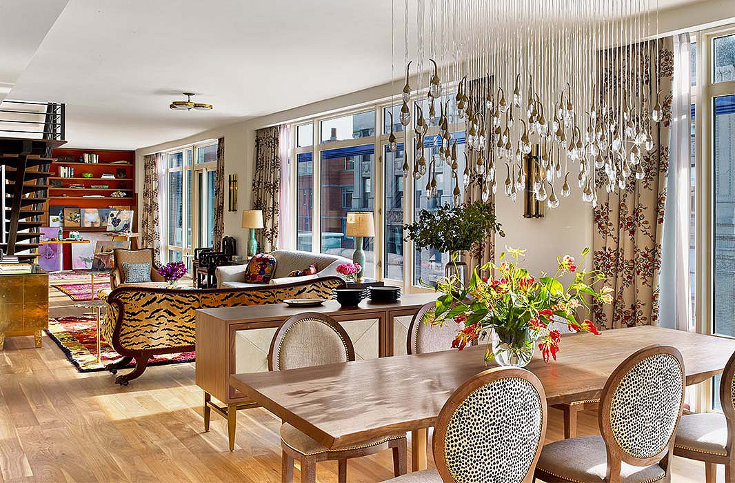 An artful chandelier gives the dining area a sense of presence above a live-edge table and chairs custom-designed by Kati. The sideboard, cleverly floated, helps to delineate the space from the rest of the apartment while providing much-needed storage.