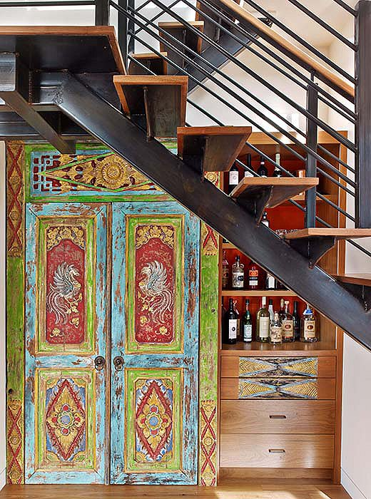 Kati transformed a niche below the stairs into a coat closet and bar using a temple door she found in Indonesia.