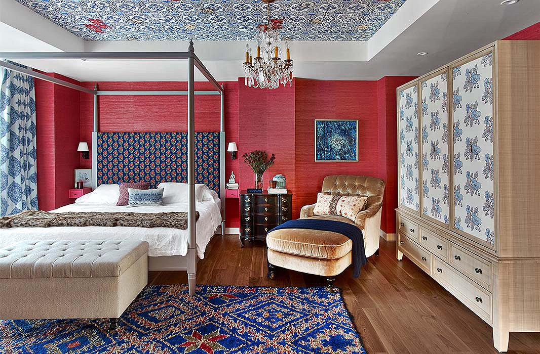 Katie wrapped a bedroom in red grass-cloth paper and dressed it with patterns of varying scale. Hints of royal and navy blues, such as those found in the rug and the headboard, temper the warmth of the walls to create an ideal space for sleep.