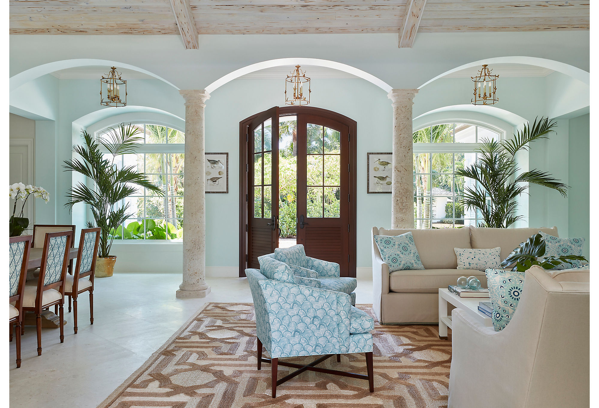 """""""We didn't want the living room to look like new construction,"""" says Caitlin. She set about aging the room with natural elements including coral, pecky cypress, and fibrous rugs."""
