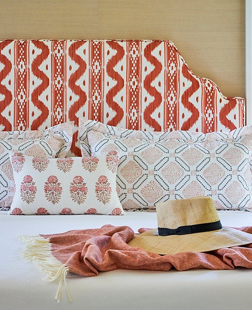 In the guest room, pops of persimmon and layers of pattern add an element of playfulness to the tropical home.