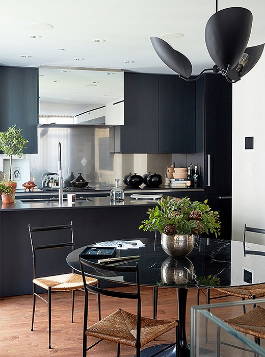 Gio Ponti chairs surround a Saarinen dining table. Kim had always wanted an all-black kitchen, and she now uses the space daily to whip up vegan dishes inspired by favorite destinations. The mirrored stove hood adds another layer of depth to the room.