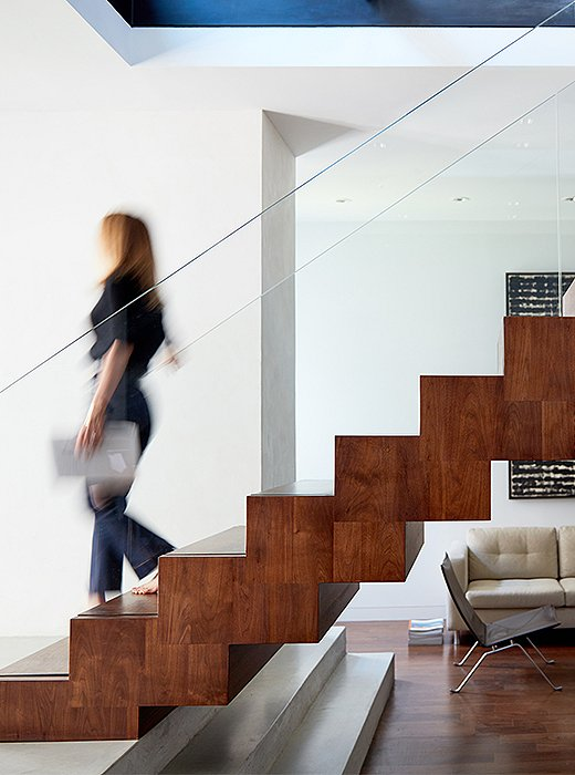 Freestanding stairs constructed of wood, steel, and glass read like a sculpture from all sides. The architects (ZH Architects) were careful to repeat materials throughout the apartment, creating a cohesive visual identity for the home.