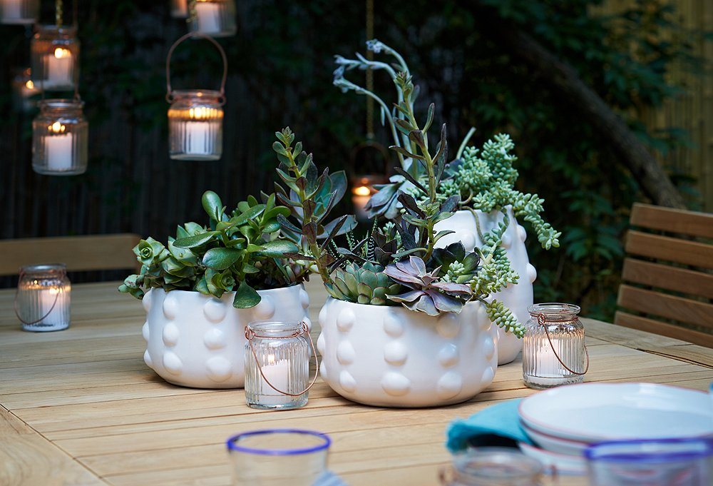 The polished and clean look of the white-on-white planters is as eye-catching on this table as it is on the ground. They can easily be mixed in with the rest of the backyard plantings.